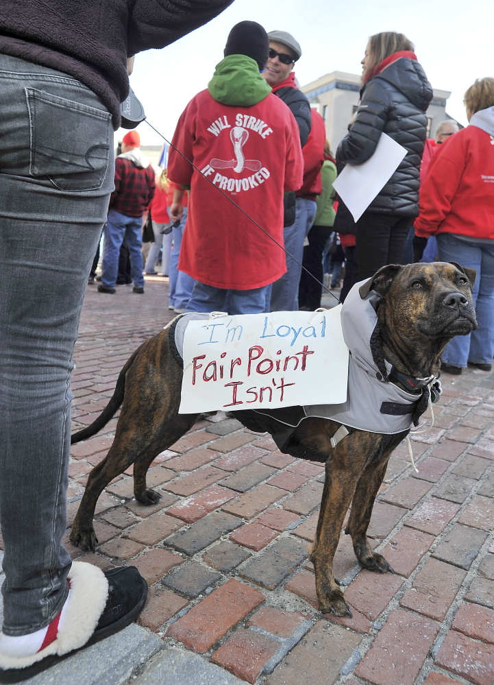 Dixon, a dog owned by Vinalhaven Fairpoint worker Patrick Shane, carries a couple of messages as he attends the striking Fairpoint union workers rally at Monument Square with Andrea Shane, his daughter, on Saturday.