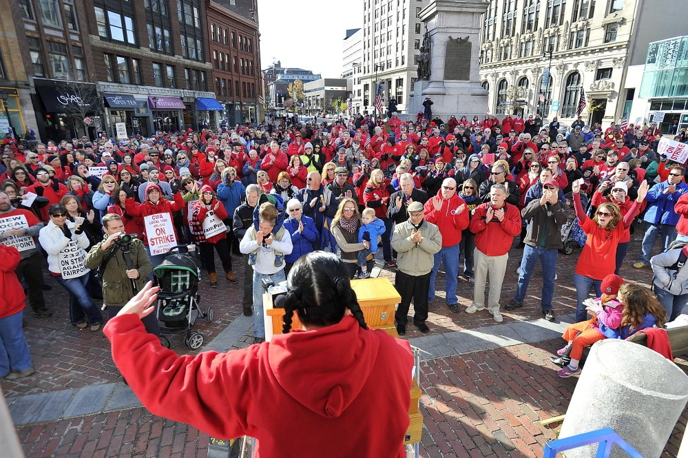 Kimberly Talbot with IBEW local 2327, sings to the crowd to get them fired up as striking Fairpoint union workers rally at Monument Square on Saturday.
