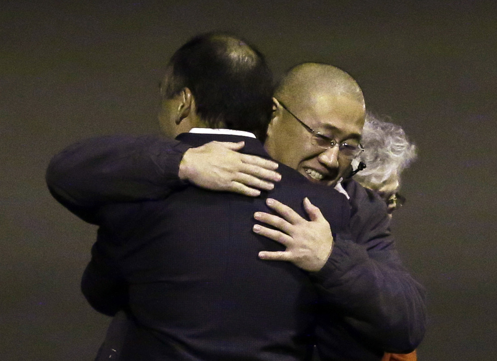 Kenneth Bae, center, who had been held in North Korea since 2012, is hugged after arriving Saturday at Joint Base Lewis-McChord, Wash.