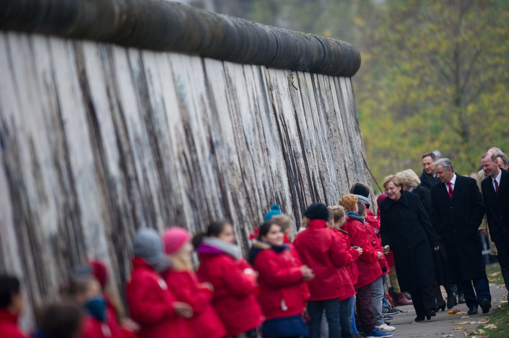 German Chancellor Angela Merkel, left, shakes hands with children symbolizing so-called Mauerspechte (wall peckers – people who chipped the wall with hammers) along remains of the Berlin Wall at the Berlin Wall memorial site at Bernauer Strasse in Berlin, Germany on Sunday.