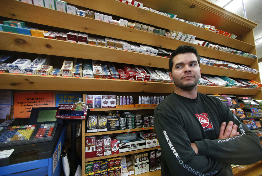 Brian Vincent poses in front of a large display of tobacco products at Vincent's Country Store in Westminster, Mass. Local officials are contemplating what could be a first: a blanket ban on all forms of tobacco and e-cigarettes, leaving some shop owners fuming.