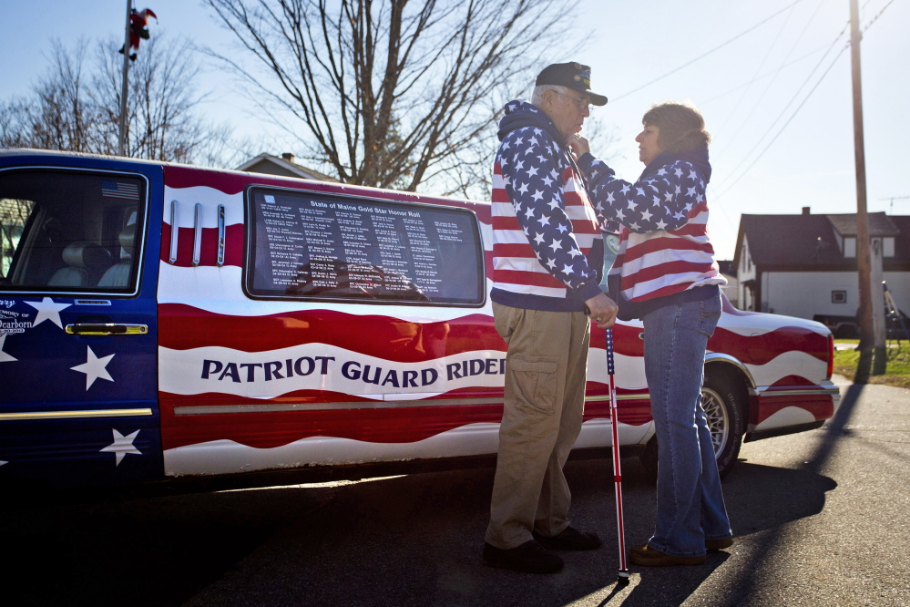 Rita Dearborn fusses over her husband's American flag sweatshirt on Saturday as they stand in front of his 1997 Lincoln Town Car Limousine that Larry Dearborn drives around the state to honor veterans of America's wars. The Dearborns plan to take part in this year's parade in Richmond.