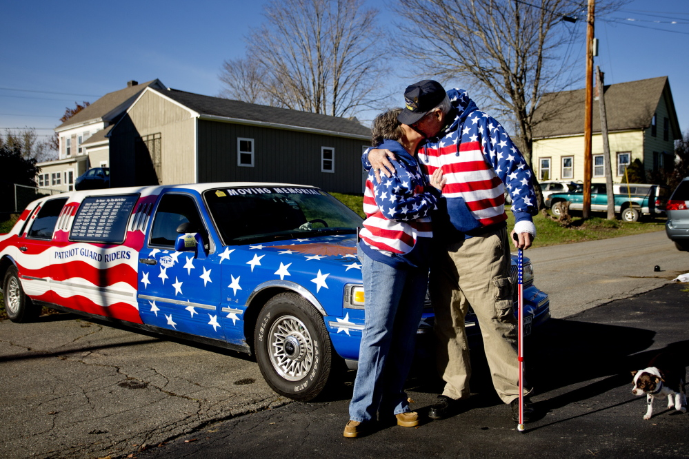 Rita Dearborn and her husband Larry share a kiss on Saturday as they stand at the front of his 1997 Lincoln Town Car Limousine that they drive around the state to honor veterans of America's wars. The Dearborns plan to take part in this year's parade in Richmond.