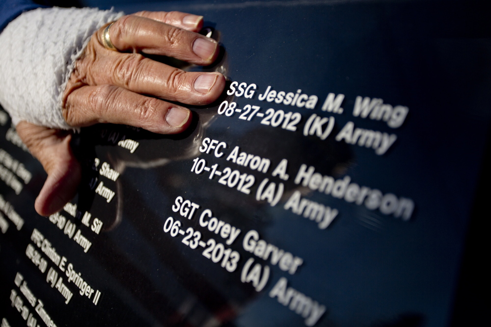Larry Dearborn of Richmond on Saturday moves his hand over the lettering on the window of his 1997 Lincoln Town Car Limousine that he and his wife Rita drive around the state to honor veterans of America's wars. Dearborn has every Maine soldier who has died in battle since 9/11 listed on the windows of his car. The Dearborns plan to take part in this year's parade in Richmond.