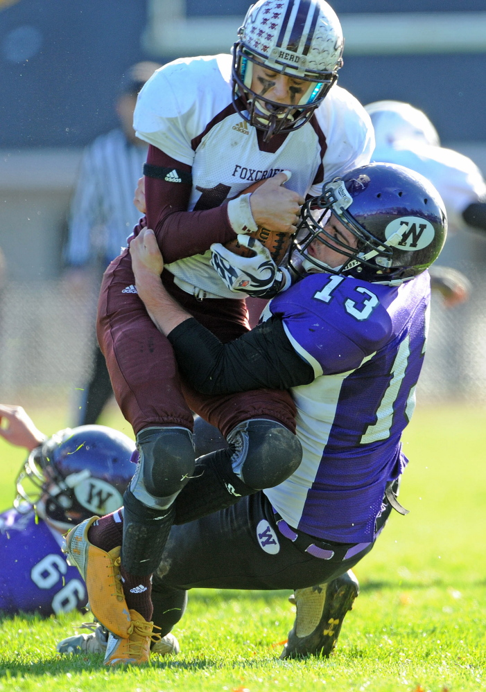 Waterville Senior High School's Trevor Gray, left, wraps up Foxcroft Academy's Hunter Smith (10) during the first half last Saturday in Waterville. The Purple Panthers play Winslow this weekend for the Eastern Class C title.