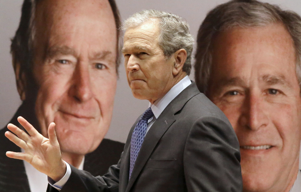 """Former President George W. Bush passes by a portrait of himself and his father former President George H.W. Bush as he takes the stage to discuss his new book, """"41: A Portrait of My Father"""" at the his father's presidential library Tuesday in College Station, Texas."""