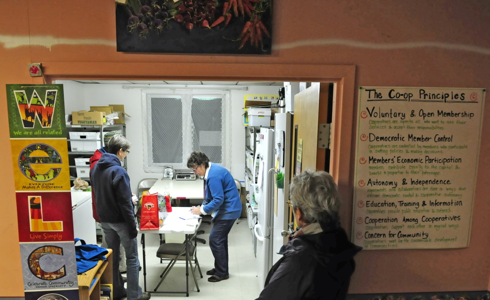 Betty Morrell, online marketplace manager for the Kennebec Local Food Initiative Online Buying Club, center, helps customer pick up their orders last week at Faith Christian Church in Gardiner. On Saturday, the group plans to announce a storefront location in downtown Gardiner.