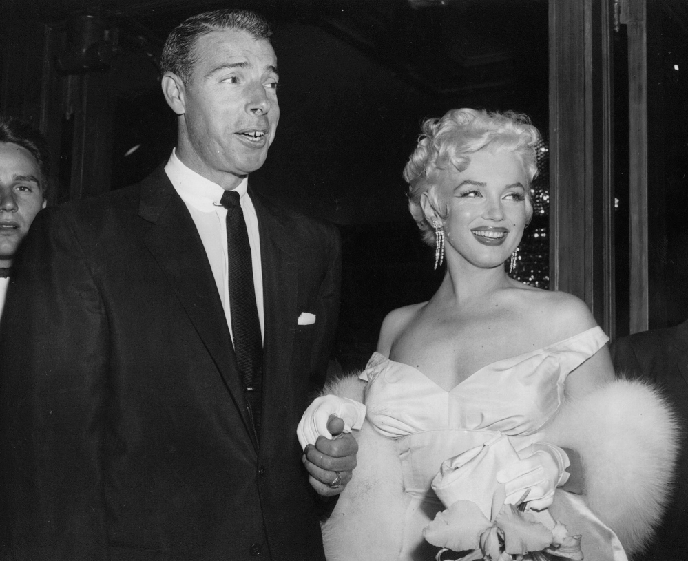 In this June 2, 1955 file photo, actress Marilyn Monroe, right, dressed in a glamorous evening gown, arrives with Joe DiMaggio at the theater.