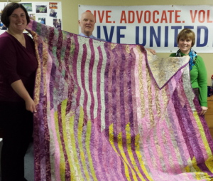 The Great Charity Auction committee members Melissa Caminiti, Bruce Williamson and Wanda Williamson show a quilt donated by committee member Wanda Williamson.