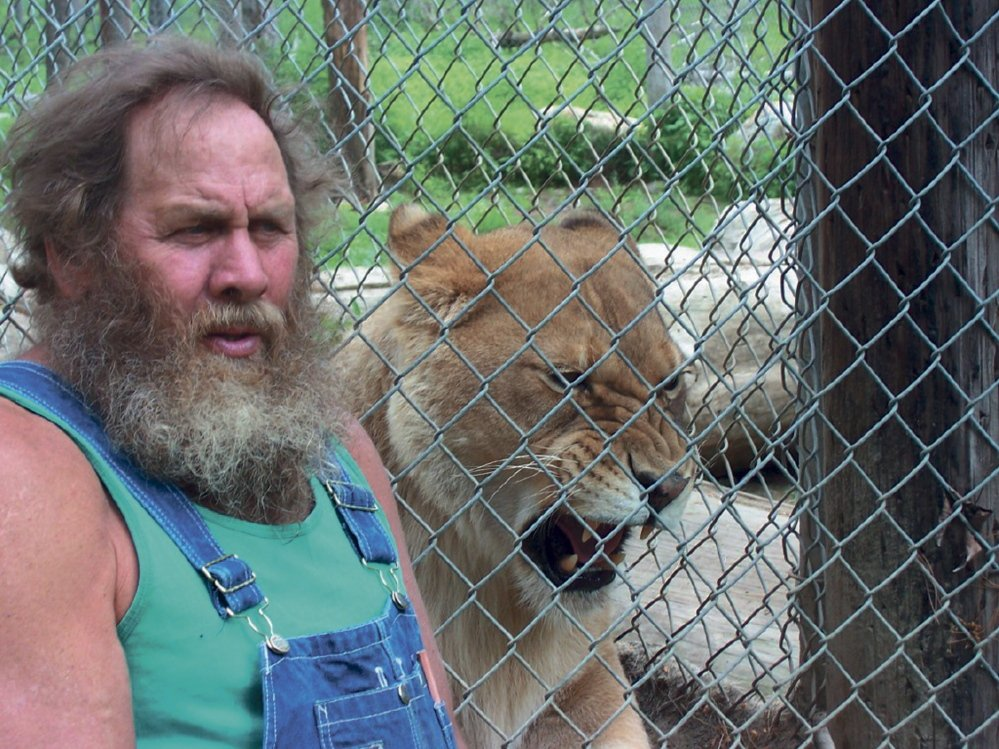 Bob Miner poses with Lilyannah, an African lion that lives at the D.E.W. Animal Kingdom & Sanctuary in Mount Vernon in this 2011 file photo.