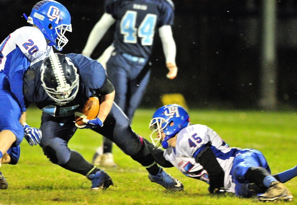 Dirigo fullback Tyler Frost, middle, is tackled by Oak Hill linebacker Levi Buteau, left, and defensive back Kyle Tervo during a Western D semifinal game last Friday.