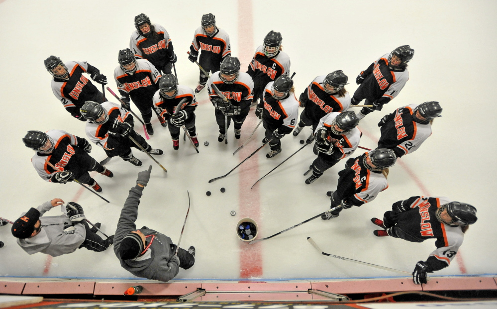 Staff photo by Michael G. Seamans   Winslow High School girls hockey coach Chris Downing, bottom left center, instructs his players during practice Thursday at Sukee Arena in Winslow.