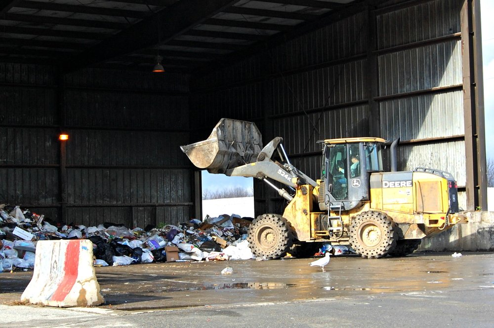 Workers at the Oakland transfer station prepare garbage for transport to an incinerator in Orrington. Garbage volume — and fee collections — are down since Waterville started requiring residents to pay for trash removal through mandatory use of official city trash bags.
