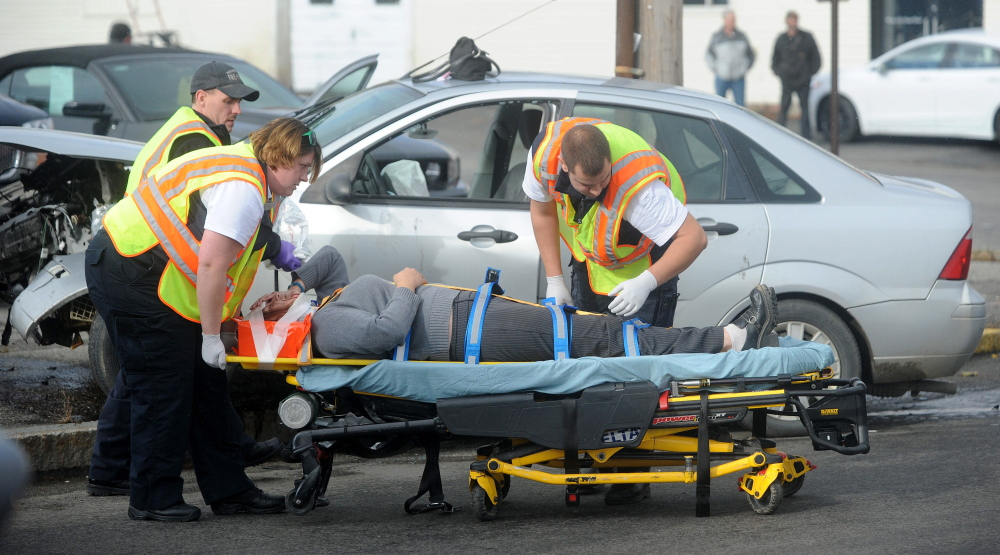 Waterville fire department and Delta Ambulance workers secure Heather Wadsworth to a stretcher after extricating her from her car after an accident at the intersection of Oak Street and College Avenue in Waterville on Friday.