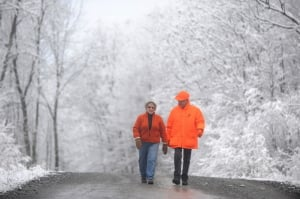 Fern and Bud Bard, of Waterville, walk along Quarry Road in Waterville early on Friday after an overnight snowfall,