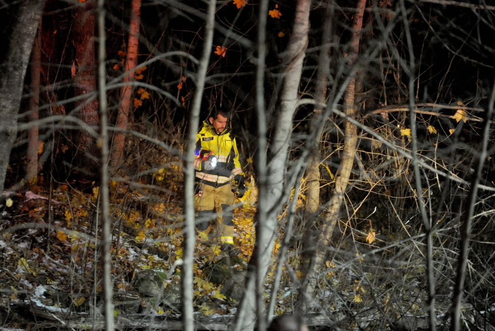 Captain Drew Corey of the Waterville fire department searches the woods for the occupants of a vehicle that crashed Rice Ripps Road near Colby College in Waterville early on Saturday morning