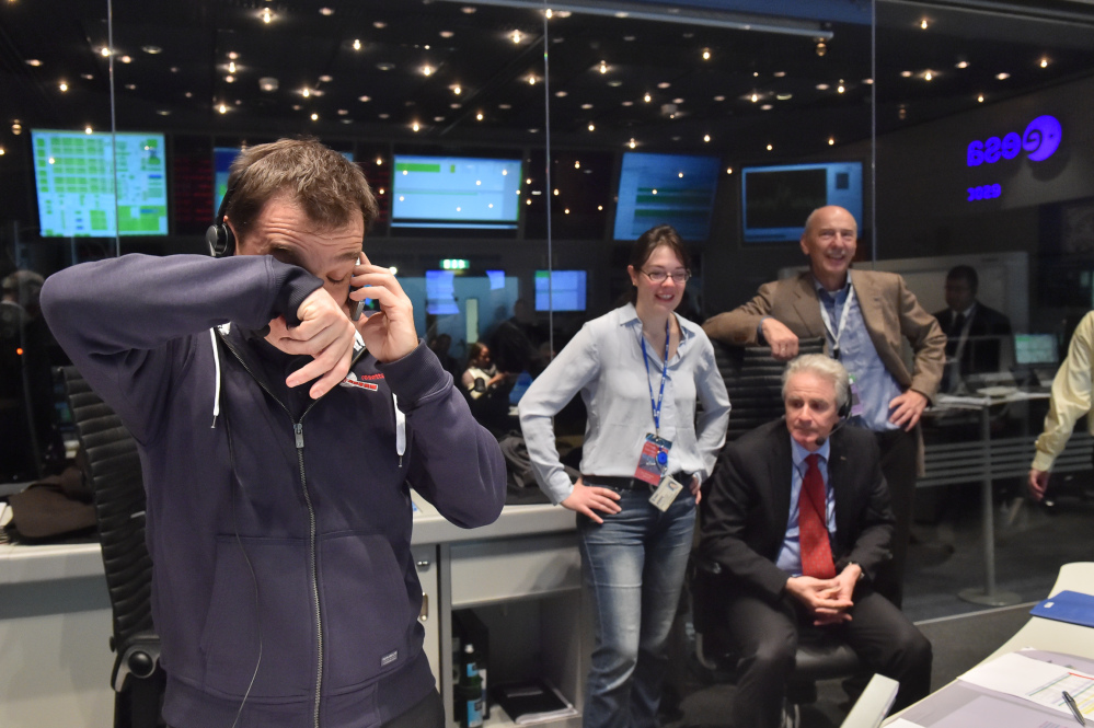 Rosetta Flight Director, Andrea Accomazzo,, left,  takes a call after receiving confirmation that the Rosetta mission's Philae lander has successfully touched down on Comet 67P/Churyumov-Gerasimenko.