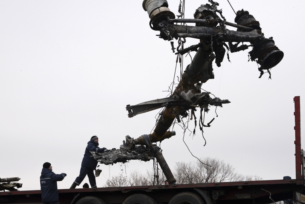 Recovery workers in rebel-controlled eastern Ukraine load debris from the crash site of Malaysia Airlines Flight 17, in Hrabove, Ukraine, Sunday, four months after the plane was brought down.