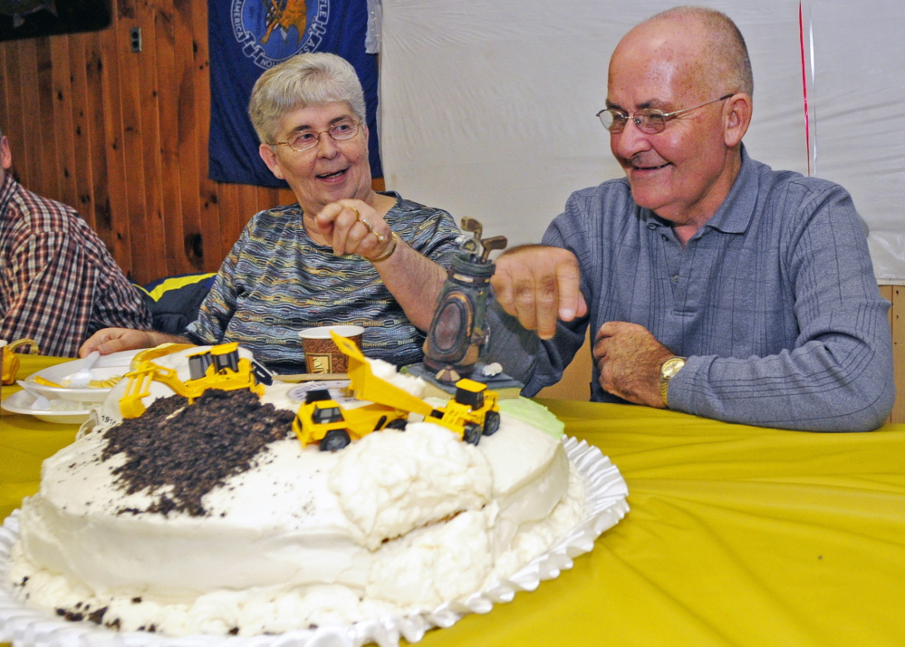 Herb Whittier, right, and his sister, Betsey Deisinger, look at the cake at his retirement party on Friday at Monmouth Fish and Game Club in Monmouth.