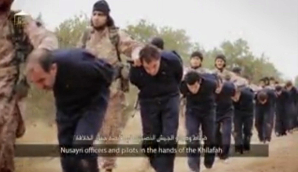 This still image taken from an undated video published on the Internet by the Islamic State group militants and made available, Sunday, purports to show extremists marching Syrian soldiers before beheading them.