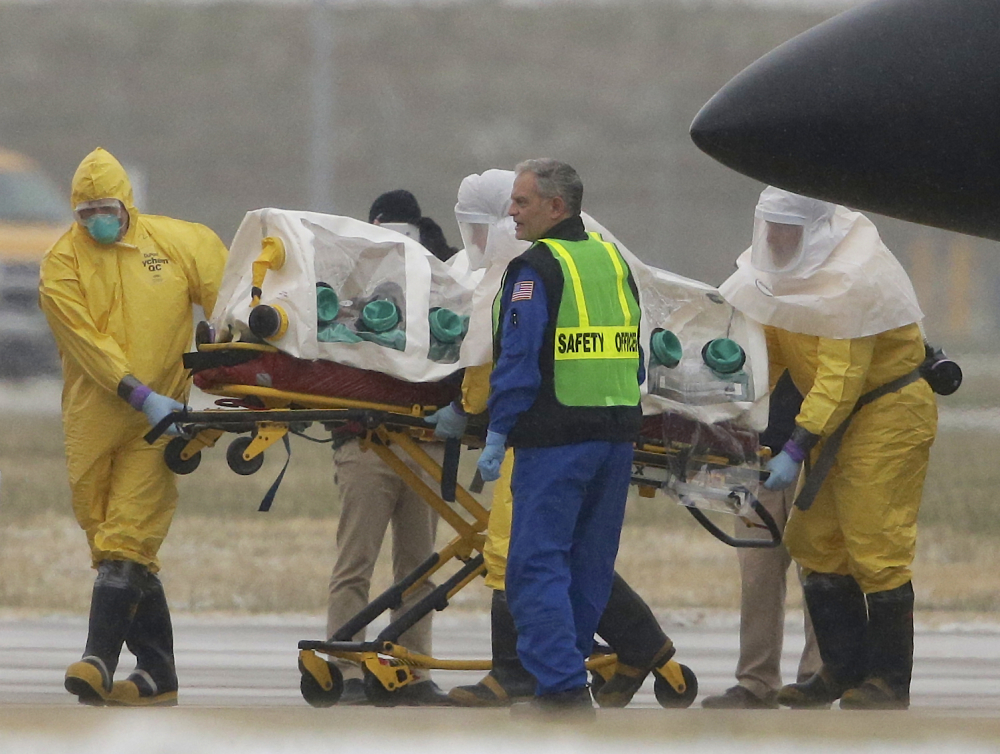 Health workers in protective suits transport Dr. Martin Salia, a surgeon working in Sierra Leone who had been diagnosed with Ebola, from a jet that brought him from Sierra Leone to a waiting ambulance that will take him to the Nebraska Medical Center in Omaha, Neb., Saturday, Nov. 15, 2014.