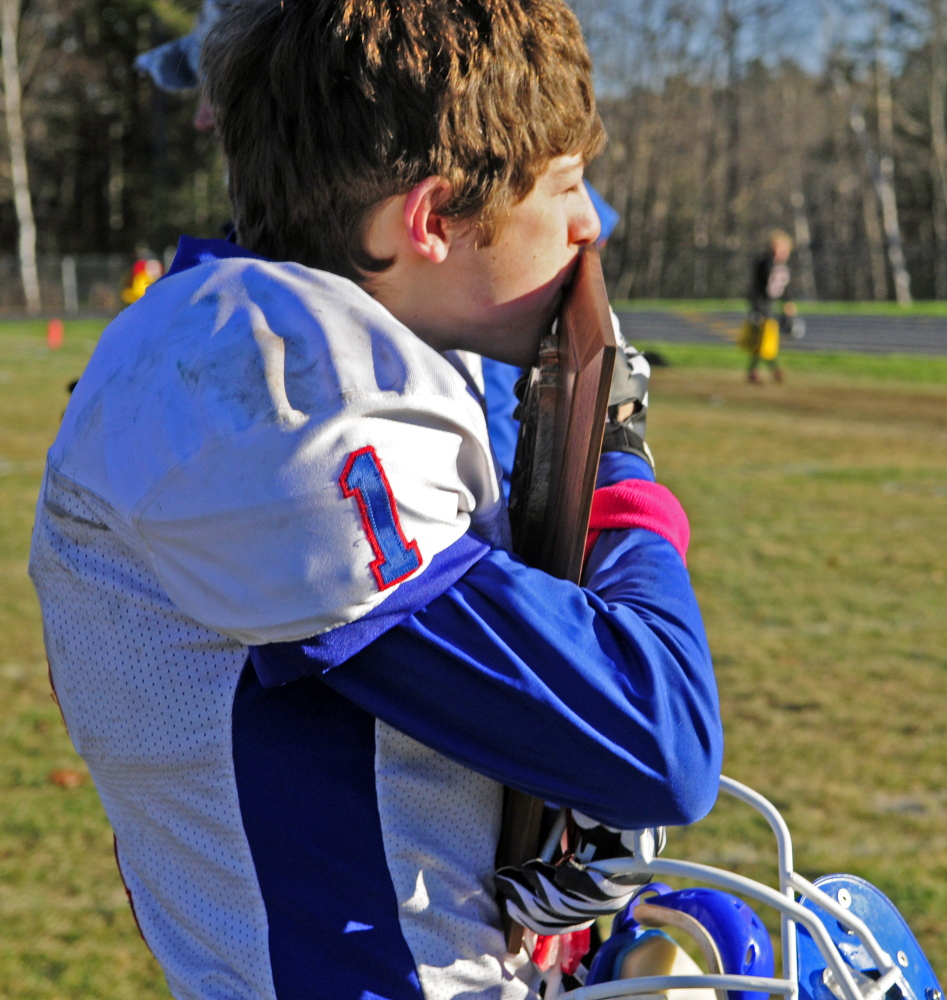 Staff photo by Joe Phelan   Oak Hill kicker Adam Merrill kisses the plaque after the Raiders won the Western D championship game Saturday in Lisbon. His point after conversion made the difference in a 7-6 victory.