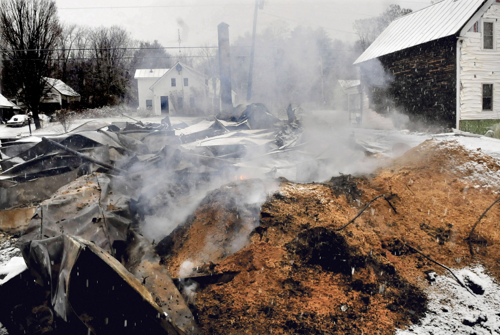 Smoke and flames rise from a large pile of pellets behind the home of Rick and Tina Belanger on Monday hours after fire destroyed their Main Street home in Caratunk. In the background is the home of Dan and Marie Beane who own the post office property and called in the fire.