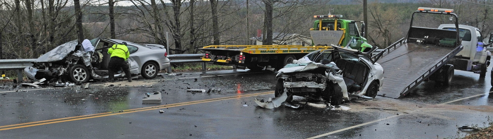 Two truck drivers clean up after State Police investigated a two vehicle head-on crash on Tuesday on Eastern Avenue just east of Pleasant Hill Road in Augusta.