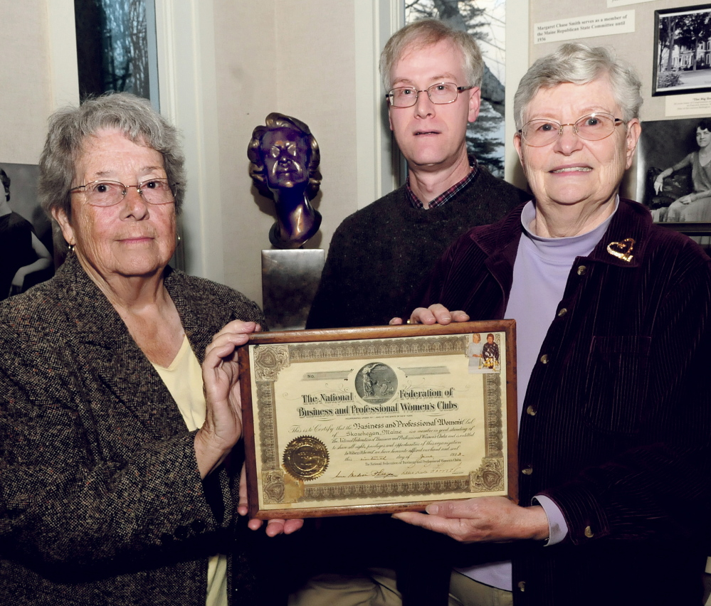 Members of the now-disbanded Skowhegan Chapter of Business and Professional Women of Maine organization Joan Slipp, left, and Marjorie Coburn Black hold an organization plaque Tuesday at the Margaret Chase Smith Library in Skowhegan. Library Director David Richards stands beside a sculpture of Smith, who co-founded the group in 1922.