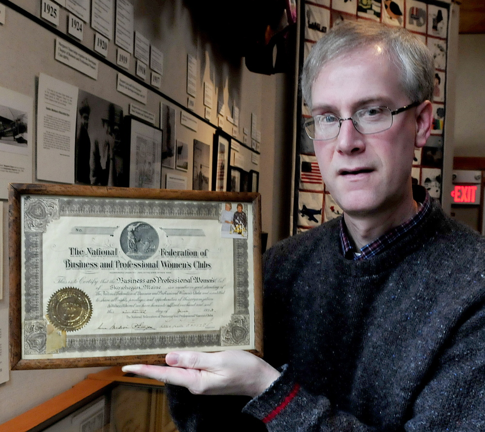 David Richards, director at the Margaret Chase Smith Library in Skowhegan holds a charter plaque of the now-disbanded Skowhegan Chapter Business and Professional Women of Maine organization on Tuesday. Smith was a founding member in 1922.
