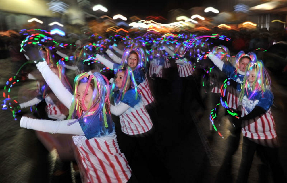 Members of the Young Americans Dance center dance their way down Main Street in downtown Waterville during the annual Parade of Lights in 2011. Lights are mandatory for all marchers during the annual festival.