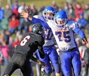 Lisbon quarterback Tyler Halls, left, just gets the pass off as Oak Hill defensive linemen Mike Pease, center, and Garrett Gile converge on the play during the Western D Campbell Conference title game last Saturday.