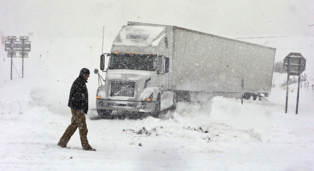 Omer Odovsc walks in front of his tractor trailer that got stuck on the 219 off ramp leading to Rt. 391 in Boston, N.Y. on Tuesday. The Buffalo Bills are doing all they can to clear off Ralph Wilson Stadium so the team can play the New York Jets on Sunday.