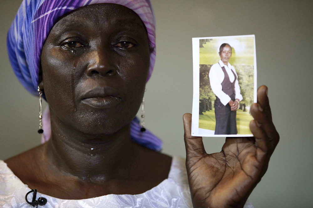"In this Monday, May 19, 2014 file photo, Martha Mark, the mother of kidnapped school girl Monica Mark cries as she displays her photo, in the family house, in Chibok, Nigeria. In a video released Oct. 31, the leader of Nigeria's Islamic extremist group Boko Haram, Abubakar Shekau dashed hopes for a prisoner exchange to get the girls released. ""The issue of the girls is long forgotten because I have long ago married them off,"" he said, laughing. (AP file photo)"
