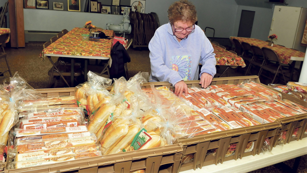 Volunteer Roberta Lessard looks over the offerings of bread at the St. Anthony's Soup Kitchen in Skowhegan on Thursday