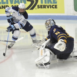 Maine winger Connor Leen (29) tries to stuff the puck around Quinnipiac goalie Eric Hartzell (33)  in the third period Saturday in Orono. Leen is second on the team with 32 shots on goal this season.