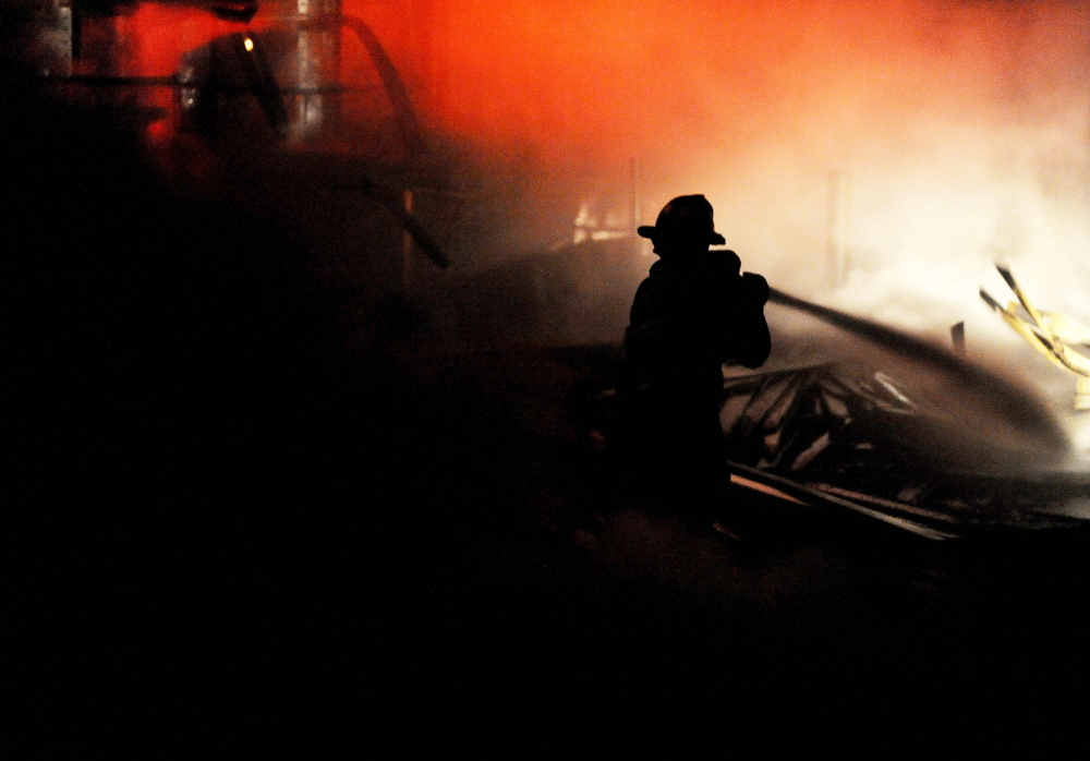 A fire burns on Thursday night at the lumber yard at Campbell's True Value Building Supply in Madison. The fire, which drew response from five area fire departments, is believed to have been started on a flatbed truck stored in the warehouse.