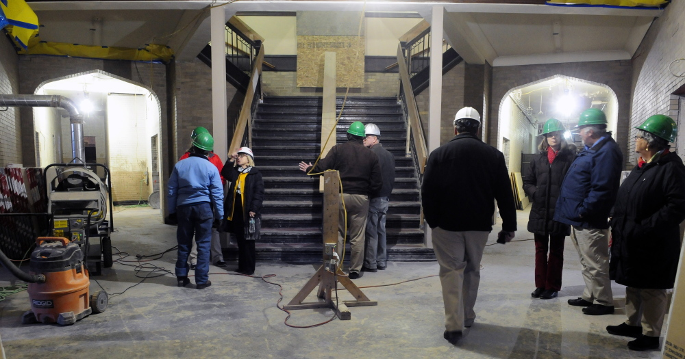 Developer Cynthia Taylor, third from left, leads a tour on Friday of the Cony flatiron building in Augusta. The former high school on Cony Circle is being renovated into apartments.