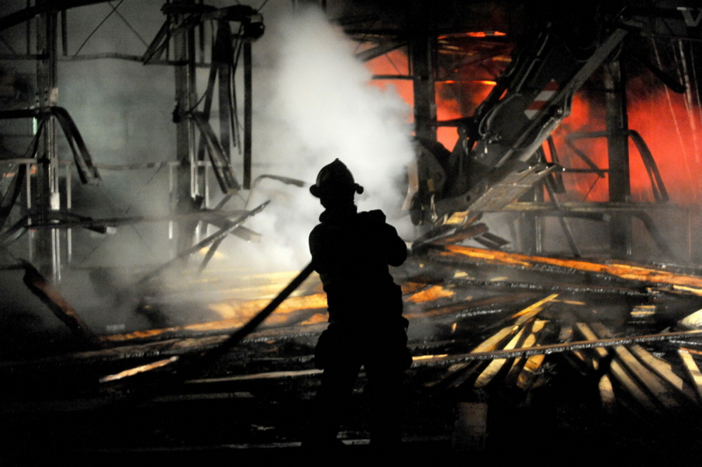A firefighter hoses down burning lumber at Campbell's True Value in Madison on Thursday night. The store owner says he was able to reopen Friday in part because of help from the community, including his competitors.