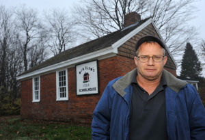 Winslow Councilman Raymond Caron, District 4, a former member of the now defunct Winslow Historical Society, stands in front of the Winslow schoolhouse on Wednesday. The school house dates to the early 1800s.