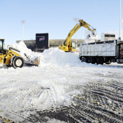 "Crews with heavy machinery remove snow outside Ralph Wilson Stadium in Orchard Park, N.Y. on Friday. Snowed out in Buffalo, the Bills are heading to Detroit to play their ""home"" NFL football game against the New York Jets on Monday night."