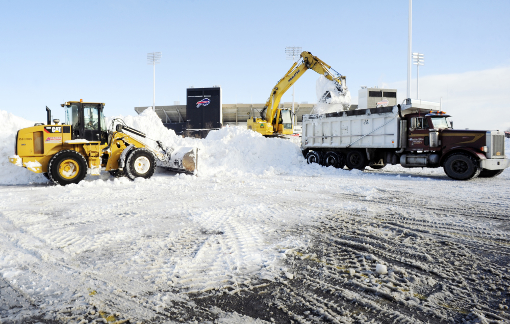 """Crews with heavy machinery remove snow outside Ralph Wilson Stadium in Orchard Park, N.Y. on Friday. Snowed out in Buffalo, the Bills are heading to Detroit to play their """"home"""" NFL football game against the New York Jets on Monday night."""