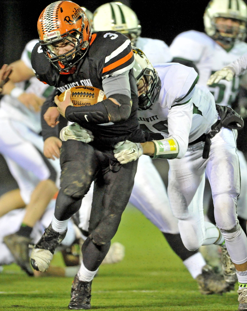 Staff photo by Michael G. Seamans   Winslow High School running back Dylan Hapworth (3) gets wrapped up by Leavit's Max Green in the first half of the Class C state title game Friday night at the University of Maine at Orono.