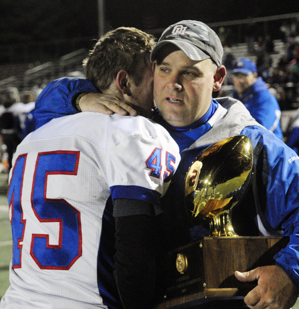 Kyle Tervo hugs Oak Hill coach Stacen Doucette after the Raiders beat MCI 41-21 to win the Class D state title Saturday.