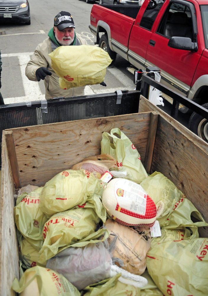 Evan Plourde tosses another frozen turkey into a trailer Saturday during a collection on Water Street in Gardiner. The frozen turkeys were being collected for the Chrysalis Place food bank to use in Christmas baskets.
