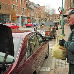 Al McMaster chats while taking a donated turkey to a trailer Saturday during a collection event on Water Street in Gardiner. The frozen turkeys were being collected for the Chrysalis Place food bank to use in Christmas baskets.