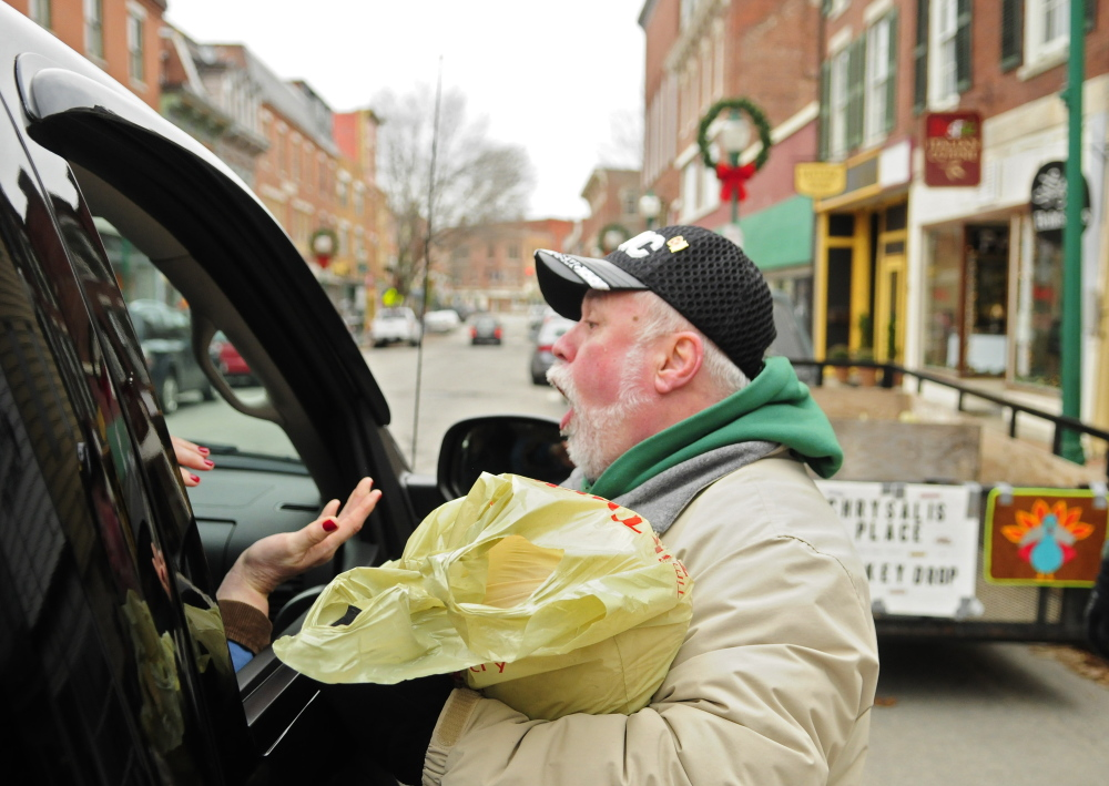Evan Plourde laughs with people who just drove up and handed him a turkey during a collection event Saturday on Water Street in Gardiner. The frozen turkeys were being collected for the Chrysalis Place food bank to use in Christmas baskets.