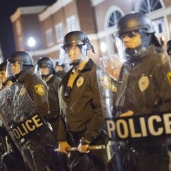 Police stand guard during a demonstration outside the Ferguson Police Department on Sunday in Ferguson, Mo. Ferguson and the St. Louis region are on edge in anticipation of the announcement by a grand jury whether to criminally charge Officer Darren Wilson in the killing of 18-year-old Michael Brown.