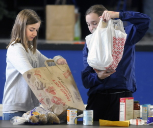 St. Michael School students Leah Allee, 13, right, and Madelyn Rancourt, 14, pack SThanksgiving baskets Sunday at the Augusta school.