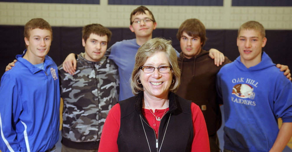 Wendy Jacobs, who coached a team of Oak Hill students at the Southern Maine Unified Basketball Tournament last spring, poses with some of her players during a practice earlier this month at the school.
